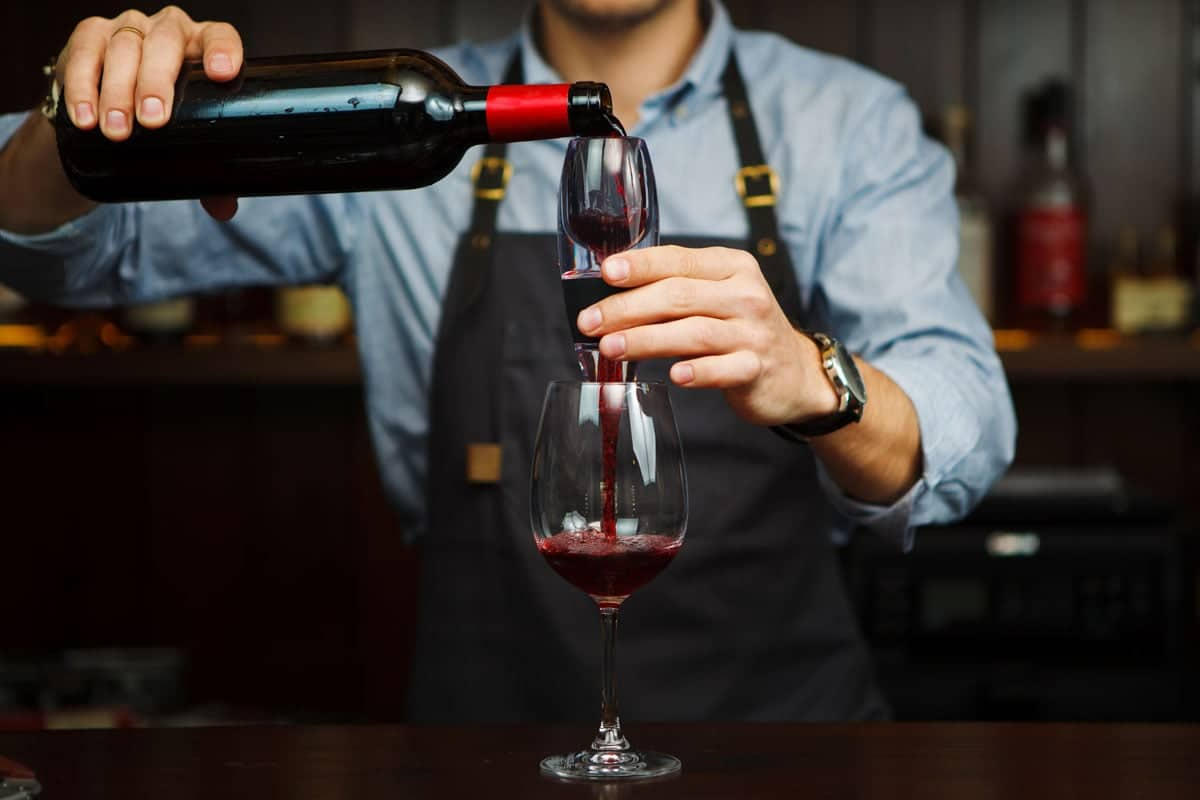 sommelier pouring red wine through aerator into glass